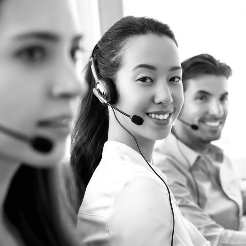 Smiling beautiful Asian woman working in call center office with international team as the customer care operators